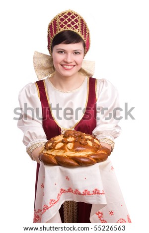 Bread-and-salt welcome. A traditional ritual of offering bread and salt to a welcome guest. Girl standing in Russian traditional costume. Woman is wearing sarafan and kokoshnik. - stock photo