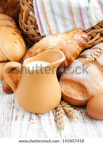 Bread and wheat corn over a old wooden background - stock photo