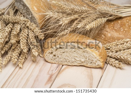 Bread and wheat ears on a wooden background.  - stock photo