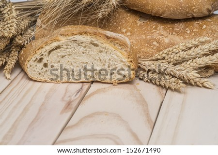 Bread and wheat ears on a wooden background.