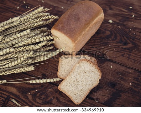Bread and wheat ears on the wooden background. Selective focus.