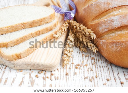 Bread and wheat on a wooden background