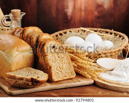 bread and wheat on the wooden background - stock photo
