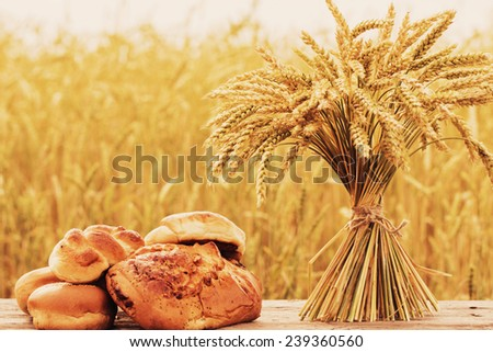 bread and wheat on the wooden table in autumn field - stock photo