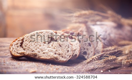 Bread and wheat on wooden table, shallow DOF, raw image. Header for website - stock photo