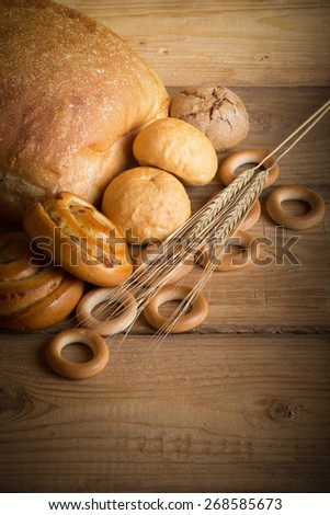Bread assortment and wheat ears on an old wooden table. Toned.