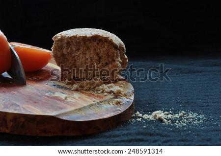 Bread Board Bread tomato and knife on a board - stock photo