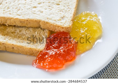 Bread, butter and jam, orange marmalade, strawberry and berry.