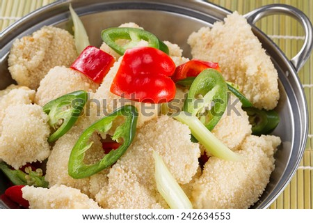 Bread coated fish and vegetables, in pan, ready to cook with natural bamboo mat background