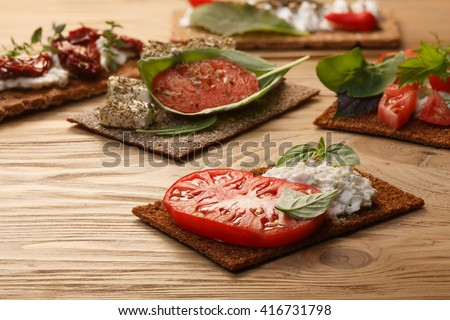 Bread crisp (crispbread open-faced sandwich) with heirloom tomato, cream cheese and fresh basil leaves on wooden table. Selective focus on foreground sandwich - stock photo