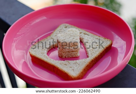 Bread cutting in shape of heart on pink dish. Concept about love. - stock photo