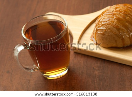 bread drizzled with honey on a wooden plate and a cup of black tea