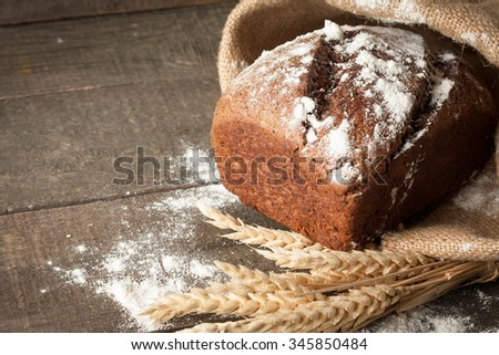 bread in rustic style retro background.Fresh traditional bread on wooden ground with flour in a sack.