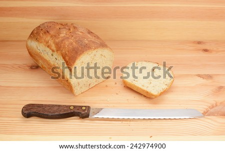 Bread knife with freshly sliced loaf of oat and linseed bread on a wooden table - stock photo