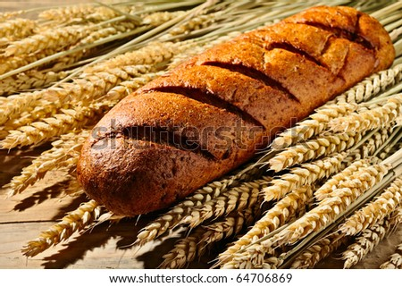 bread lying on the ears of wheat - stock photo