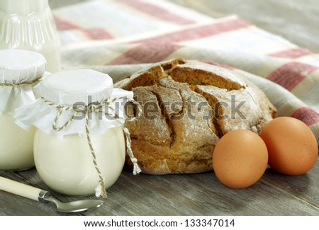 Bread, milk, eggs and yogurt on a wooden table