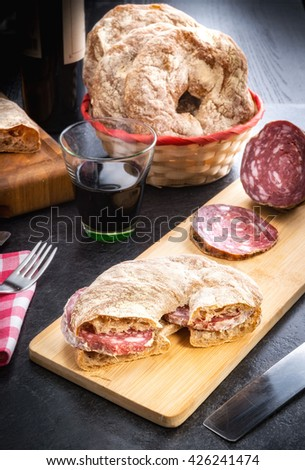 Bread of Valtellina cut and filled with Italian salami served on a wooden board accompanied by red wine - stock photo