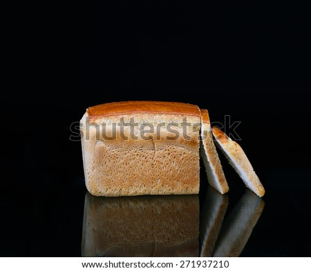 Bread on a black background with reflection - stock photo