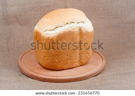 Bread on a wooden board on a background of the canvas. - stock photo