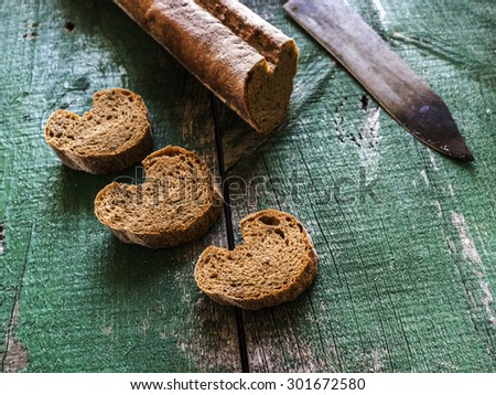 Bread on old weathering wooden table - stock photo