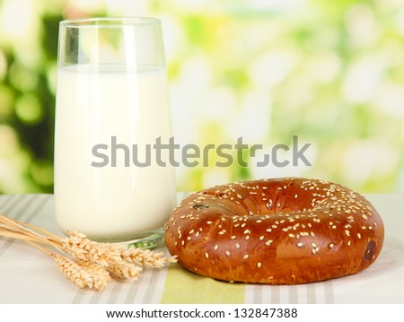 Bread roll and glass of milk on nature background - stock photo