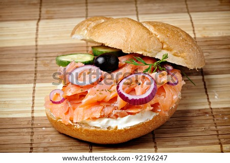 bread roll served with sliced smoked salmon, onion and olive