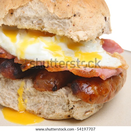 Bread roll with fried egg, bacon and sausages. - stock photo