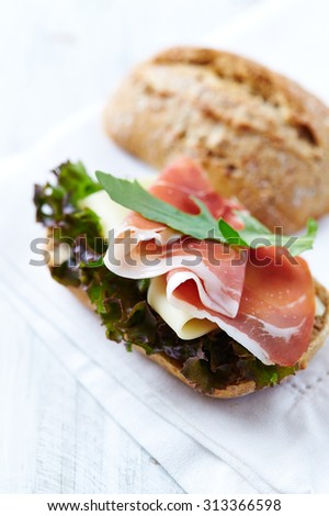 Bread roll with serrano ham and arugula  - stock photo