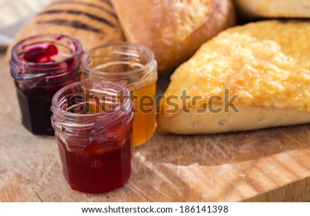bread-rolls on the cutting board with small jars of jam