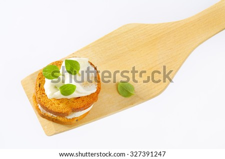 bread rusks with cream cheese on wooden spatula