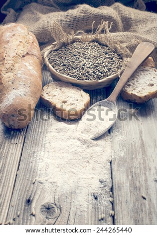 Bread, rye and a spoon with white wheat - stock photo