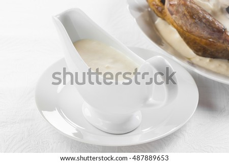 Bread sauce with cream to the fowl in faience gravy boat on a white background, horizontal