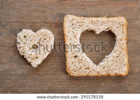 Bread slice with cut in shape of heart on wooden background