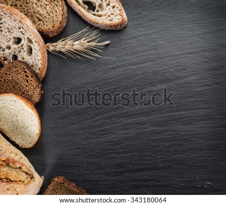 Bread slices, a wheat and a knife on the black stone desk. - stock photo