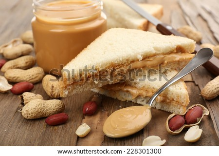 Bread slices with creamy peanut butter on wooden table - stock photo