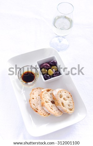 Bread slices with mixed olives and a olive oil and balsamic vinegar dip accompanied with a glass of white wine
