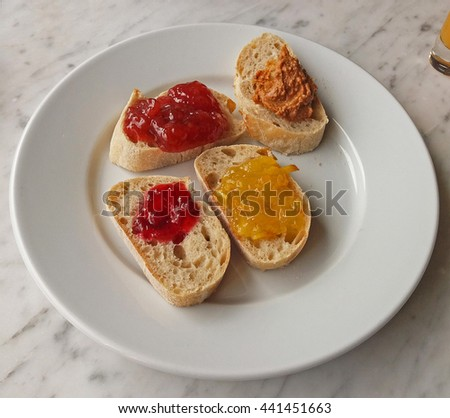 Bread slices with orange marmalade, strawberry jam, redberry jam and peanut butter