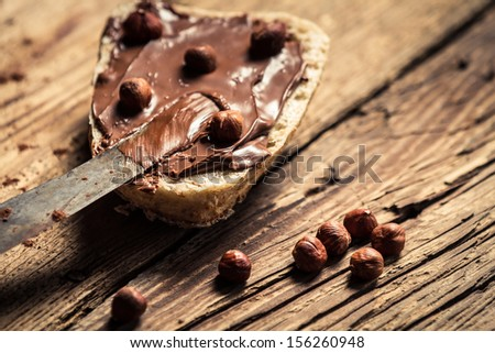 Bread spread with chocolate butter with nuts - stock photo