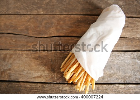 Bread sticks grissini with sesame seeds in craft pack on a wooden background - stock photo