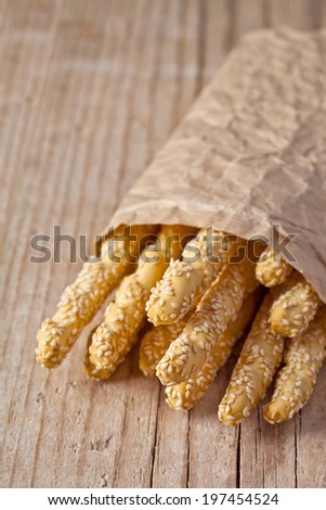 bread sticks grissini with sesame seeds in craft pack on rustic wooden background - stock photo
