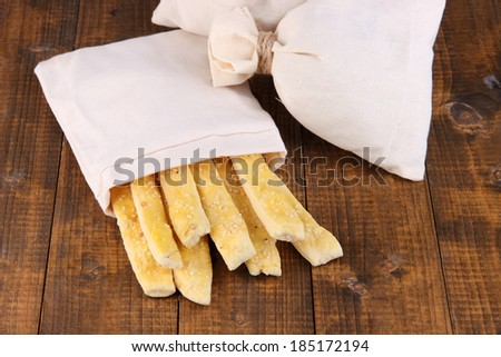 Bread sticks  in sack on wooden background - stock photo