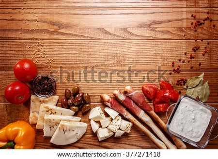 Bread sticks with prosciutto Cured Meat on a wooden table with pita bread, red tomatoes, olives, cheese and other ingredients for a lunch snack - stock photo