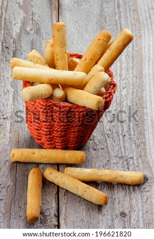 Bread Sticks with Sesame Seeds in Red Wicker Basket on Rustic Wooden background - stock photo