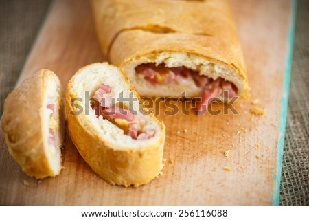 bread stuffed with cheese and bacon on a wooden board - stock photo