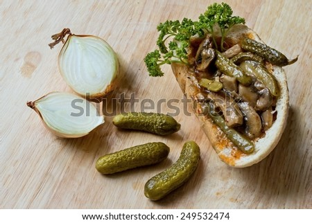 Bread stuffed with pork fillet and pickled cucumbers - stock photo