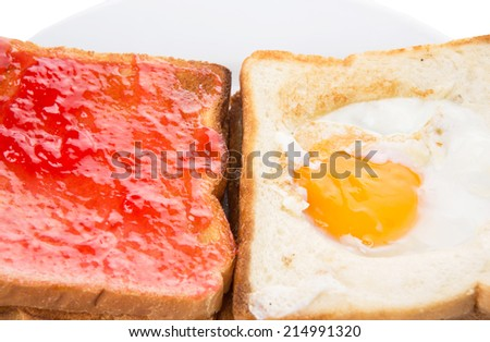 Bread toast with fried egg and strawberry jam
