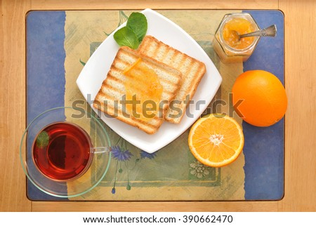bread toast with orange marmalade. black tea with mint and oranges on the tray. Breakfast in the morning. top view - stock photo