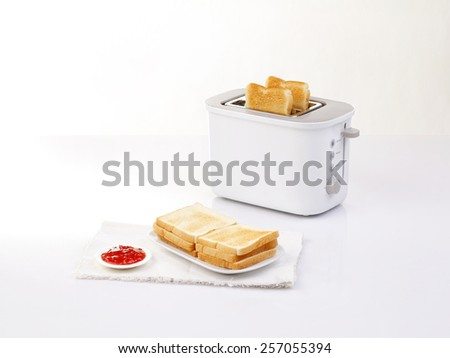 bread toaster and toasted bread served with jam - stock photo