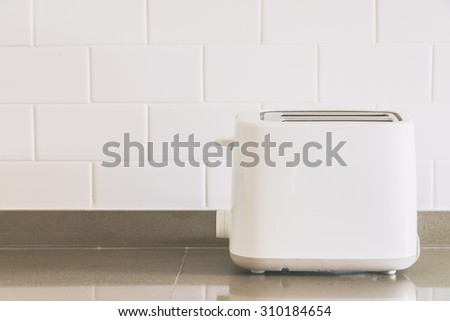 Bread toaster at kitchen - light vintage tone filter effect - stock photo
