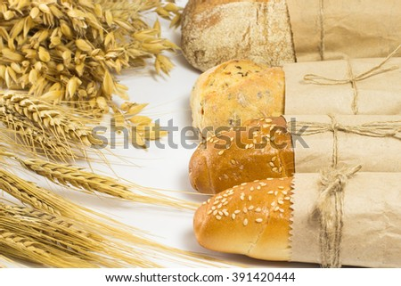 Bread, wheat and oats on a white background